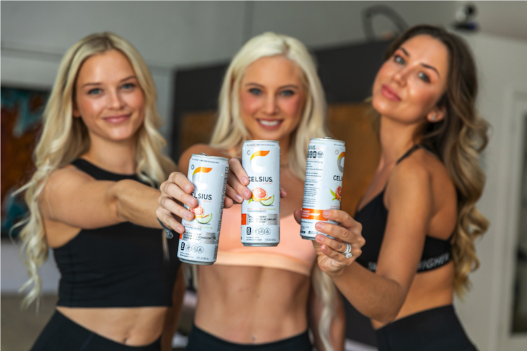 image of three women holding out cans of celsius