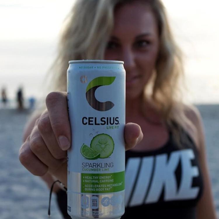 image of a woman holding out a sparkling cucumber lime celsius can