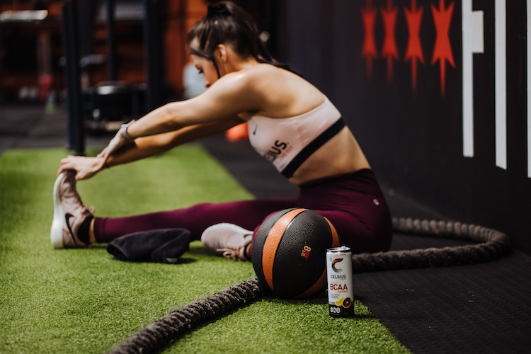 image of woman stretching in celsius apparel next to a can of celsius
