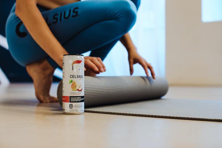 image of a woman rolling out a yoga mat wearing celsius apparel behind a can of sparkling fuji apple pear celsius