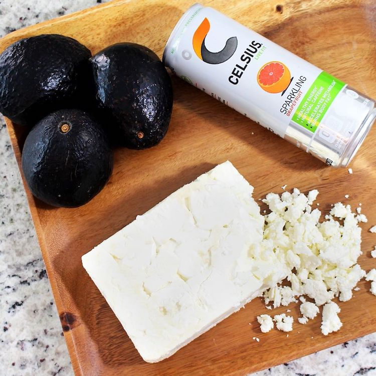 image of a sparkling grapefruit celsius on a cutting board with feta cheese and avocados