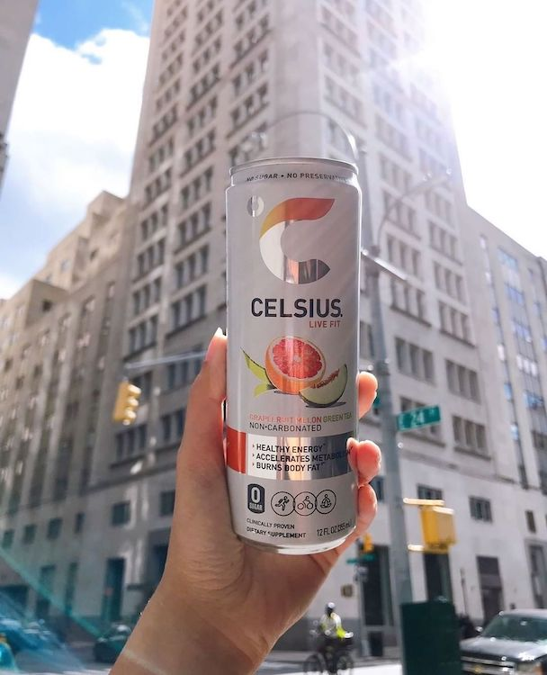 image of a grapefruit melon green tea celsius can in front of a building