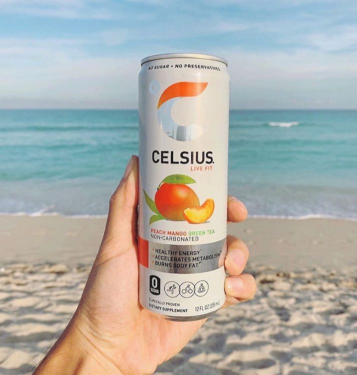 image of a peach mango green tea celsius can held in front of the ocean