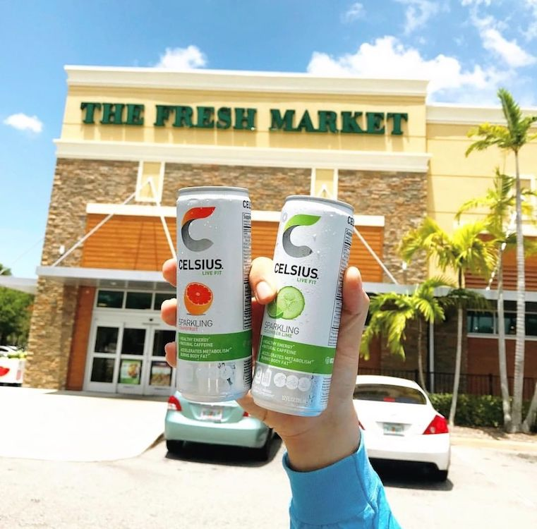 image of someone holding two celsius in front of the fresh market