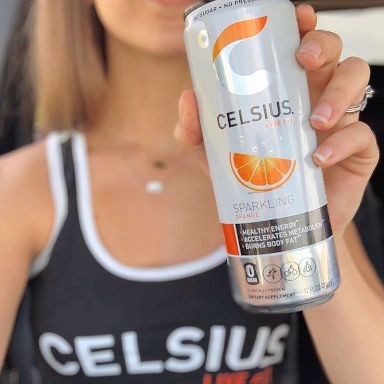 image of a sparkling orange celsius can being help by a woman in celsius apparel