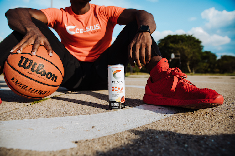 image of a man sitting next to a basketball and a bcaa celsius can