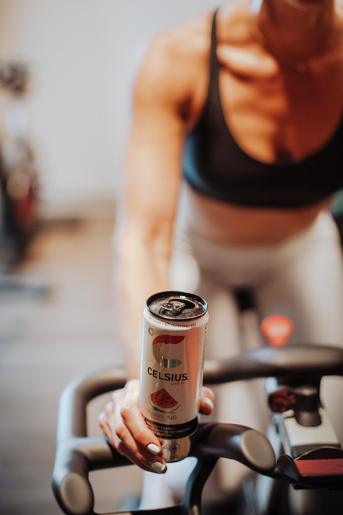 image of a woman on a stationary bike holding a celsius