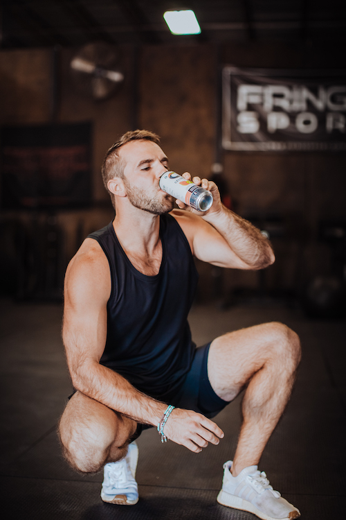 image of a man squatting drinking a celsius
