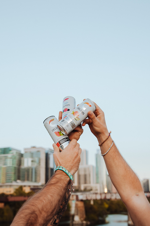image of three people holding their celsius cans together in the air