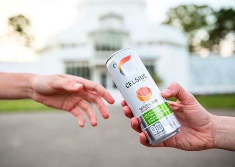image of a person handing someone a sparkling grapefruit celsius can