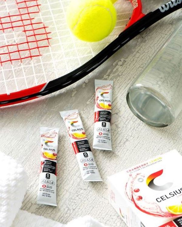 image of celsius on the go powder packets and a tennis racket and tennis balls